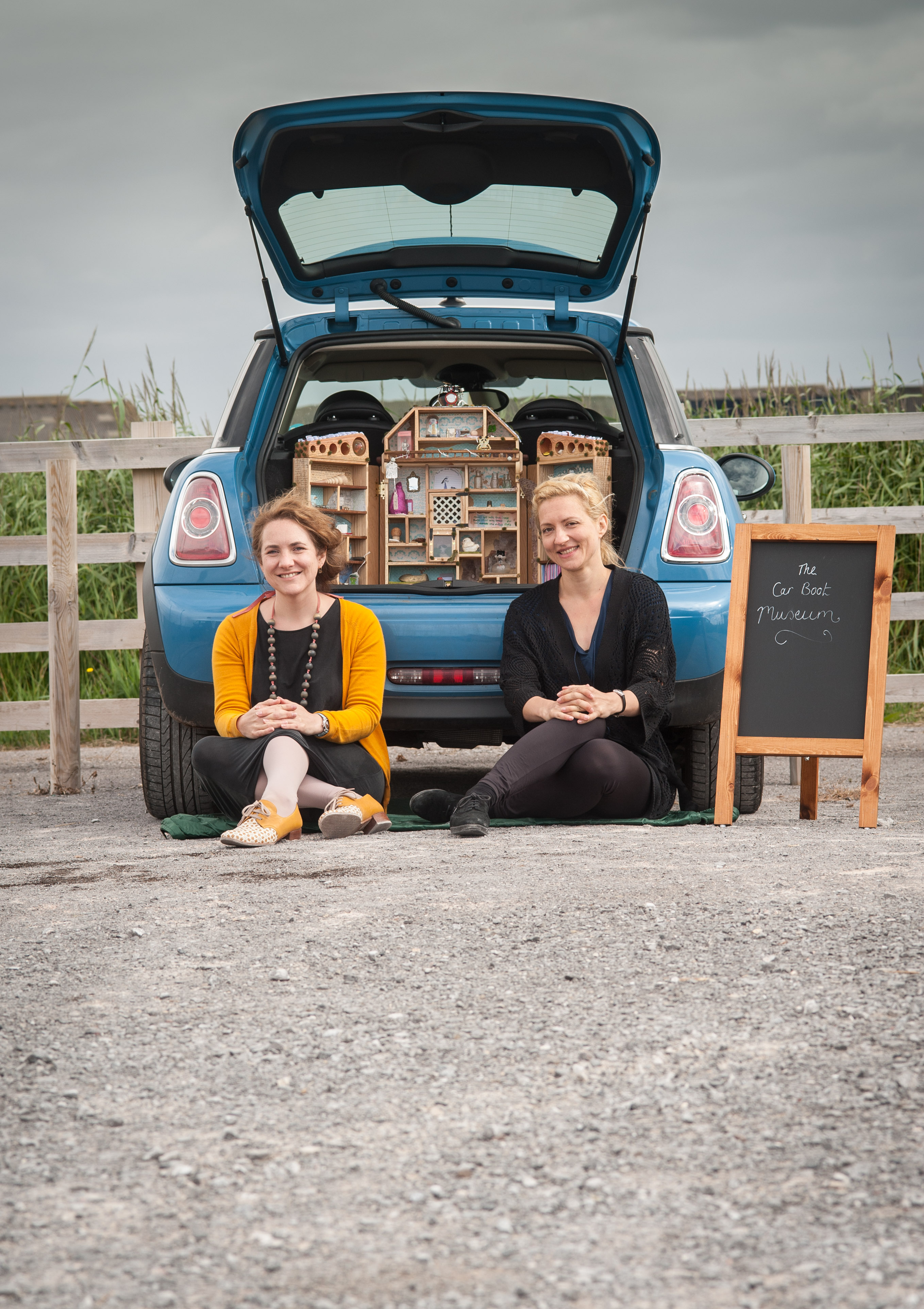 "Alice Maddicott (left) and Ana Seferovic with their miniature museum in a car boot touring scenic locations, roadsides, towns and villages around Somerset. Picture by Clint Randall www.pixelprphotography.co.uk A car boot containing a miniature museum Is popping up at scenic locations, roadsides, towns and villages around Somerset. The Car Boot Museum's specially created wooden cabinet houses a collection of everyday objects, text and images put together by artist and writer Alice Maddicott. She is joined on the tour by poet Ana Seferovic to create a collaborative poetic travelogue. The project has been commissioned by Somerset Art Works for this year's Arts Weeks Festival. Alice is touring her home county to discover the secret stories behind objects and the local landscape. Visitors are invited to bring along their own objects which can be donated to the Museum or be recorded and taken away again. People can write their own ideas and memories of the area and add them to the Car Boot Museum. Alice said: ""I would love people to bring along objects with a special memory for them or an interesting tale to tell. We rely so much on storing information digitally now, but I'd like to move away from that and to find out about the stories behind real objects. Sometimes an object has no value except to the person for whom it holds a special memory. I'd like people to share those stories."" The mini museum will evolve and change as it travels around the county. Each day it will be inspired by the places it visits and the new objects it acquires. The Car Boot Museum is winding its way along Somerset's roads, visiting Priddy Village green, Steart Marshes, Dunkery Beacon, Burrow Mump, Minehead and a range of other locations, ending up at Nunney Market Place on Sunday 9 August. Alice is using the objects and stories she gathers along the way to create an installation with sound and film for Somerset Art Weeks Festival. Alice was inspired by the theme for"